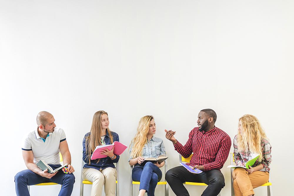 grupo de personas sentados hablando y tomando nota en cuadernos