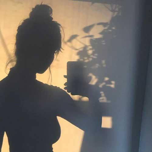 sombra en una pared de la silueta de una mujer sosteniendo un celular con su mano