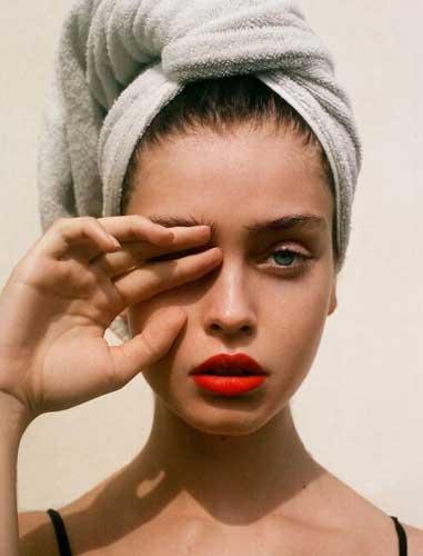 mujer con una toalla en la cabeza tapándose con una mano uno de sus ojos