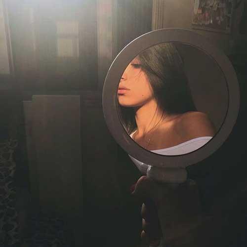 espejo que refleja la imagen de parte del perfil de una mujer