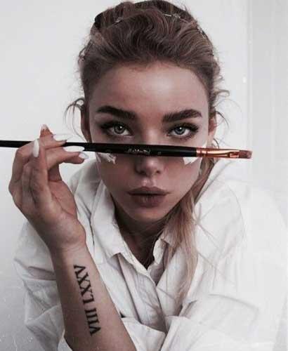chica con un pincel de pintura sobre su nariz