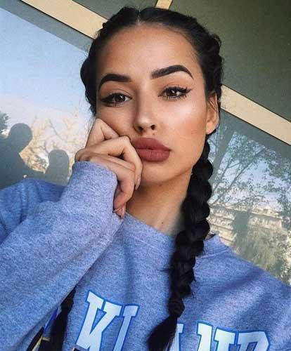 chica de trenzas maquillada mirando a camara y sosteniendo su cara con su mano sobre su boca