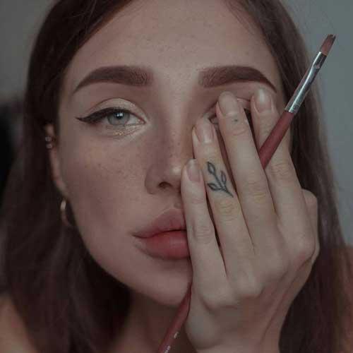 mujer mirando a cámara tapando uno de sus ojos con los dedos de su mano que sostienen un pincel de pintura limpio