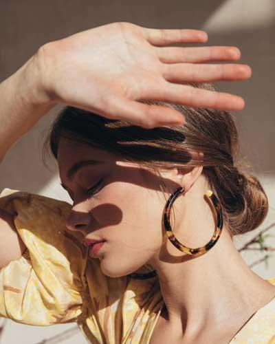 mujer tapándose su cara con una de sus manos de la luz del sol