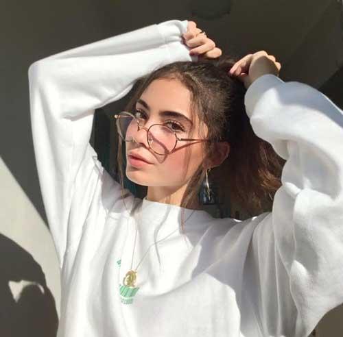 chica de lentes acomodándose su colita de pelo
