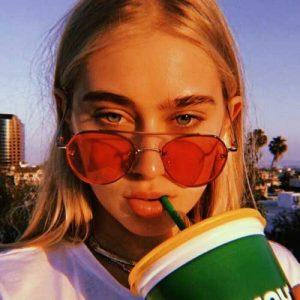 chica con lentes de color rojo tomando de un vaso con sorbete