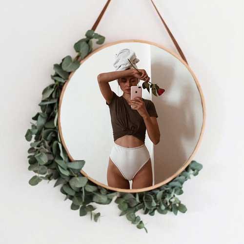 espejo colgado en una pared blanca que refleja el cuerpo de una mujer sosteniendo una flor rosa