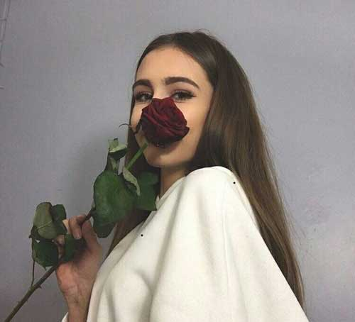 chica con una flor de rosa roja sobre su cara